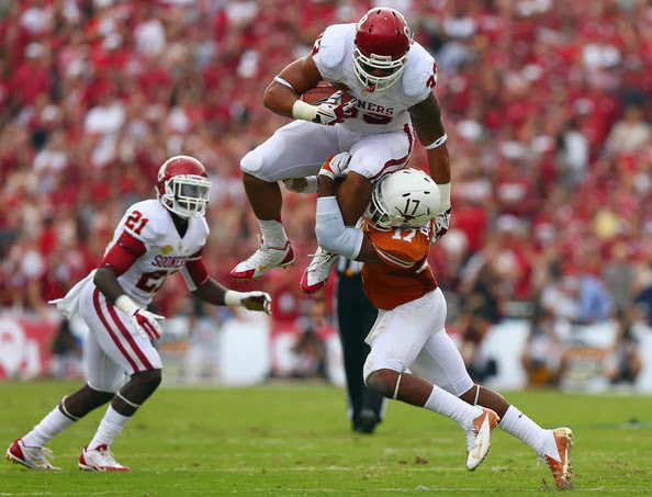 Trey Millard #33 of the Oklahoma Sooners carries the ball against Adrian Phillips #17 of the Texas Longhorns as Keith Ford #21 of the Oklahoma Sooners looks on in the first quarter at the Cotton Bowl on October 12, 2013 in Dallas, Texas. (October 11, 2013 - Source: Tom Pennington/Getty Images North America)
