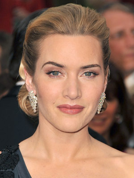 Kate Winslet rolls her wavy hair under and pins it back for a soft, chic hairstyle.