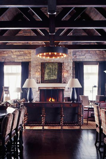 Living room with exposed beams, a round chandelier, a stone fireplace built into a rock wall, dark wood floor and a console table with two lamps with black bases