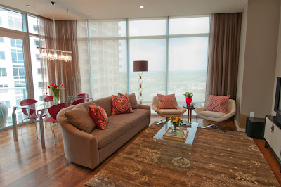 floor to ceiling windows provide plenty of lights and city view for this living room and dining area in soft color palette