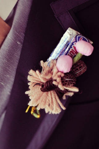 Boutonnière made with chocolates accented with crepe paper buds and yarn