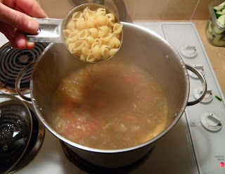 Hand Adding Measured Pasta to Boiling Soup