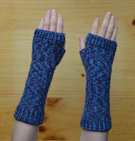 A pair of fingerless mitts with extra length at the wrists extending two thirds of the way up the forearm.  This view is looking down at the back of the hands.