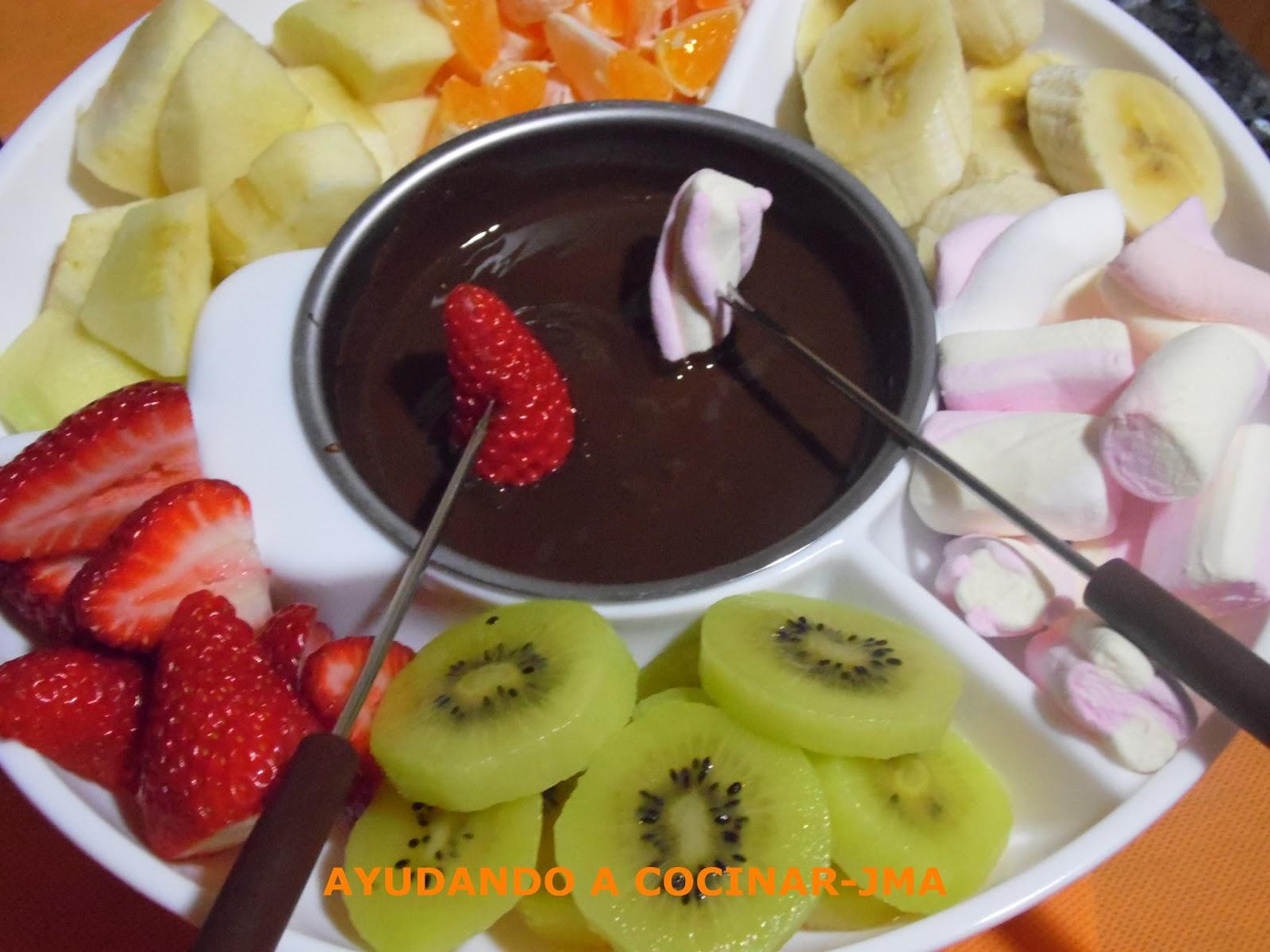 Ayudando a cocinar fondue de chocolate negro con frutas variadas