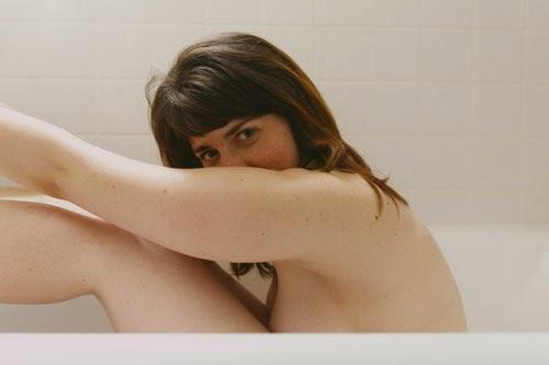 A foto mostra uma mulher nua, sentada dentro de uma banheira, de perfil, com as pernas um pouco levantadas e seus braços em cima de suas pernas. Seu rosto está levemente encoberto pelo seu braço. Grande parte de seu corpo não está aparecendo. Na foto aparece das axilas para cima.