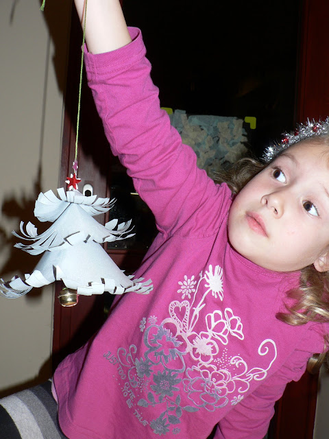 child proudly showing finished christmas craft decoration