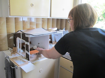 Woman rearranging furniture in a dry-fitted modern miniature doll's house shed on a kitchen bench.