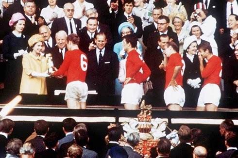 Capitão inglês Bobby Moore recebendo a taça Jules Rimet das mãos da rainha.