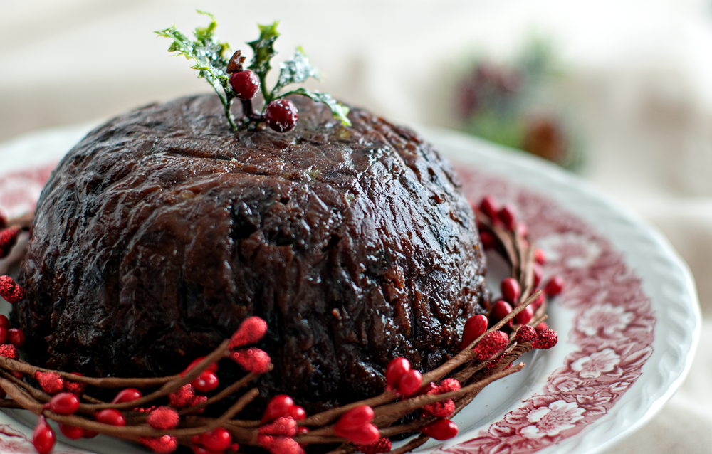 Christmas pudding decorated with holly and read berries for presentation