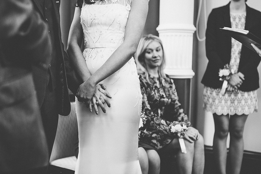 couple holding hands during wedding ceremony black and white photo