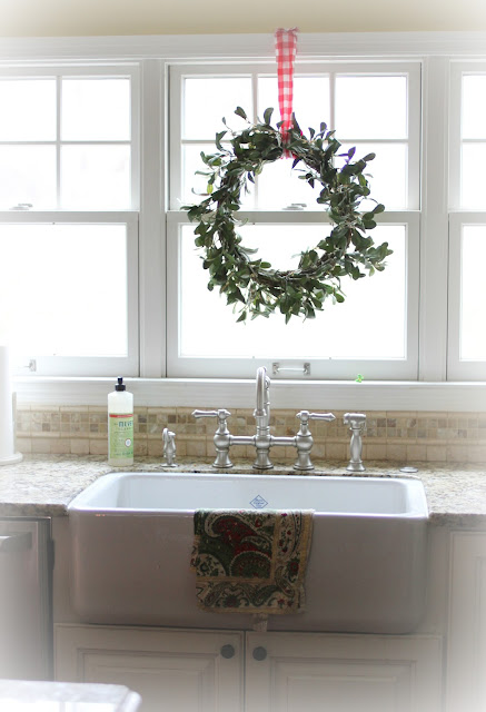 Mistletoe wreath with red buffalo check ribbon over Shaw's farm sink via www.goldenboysandme.com