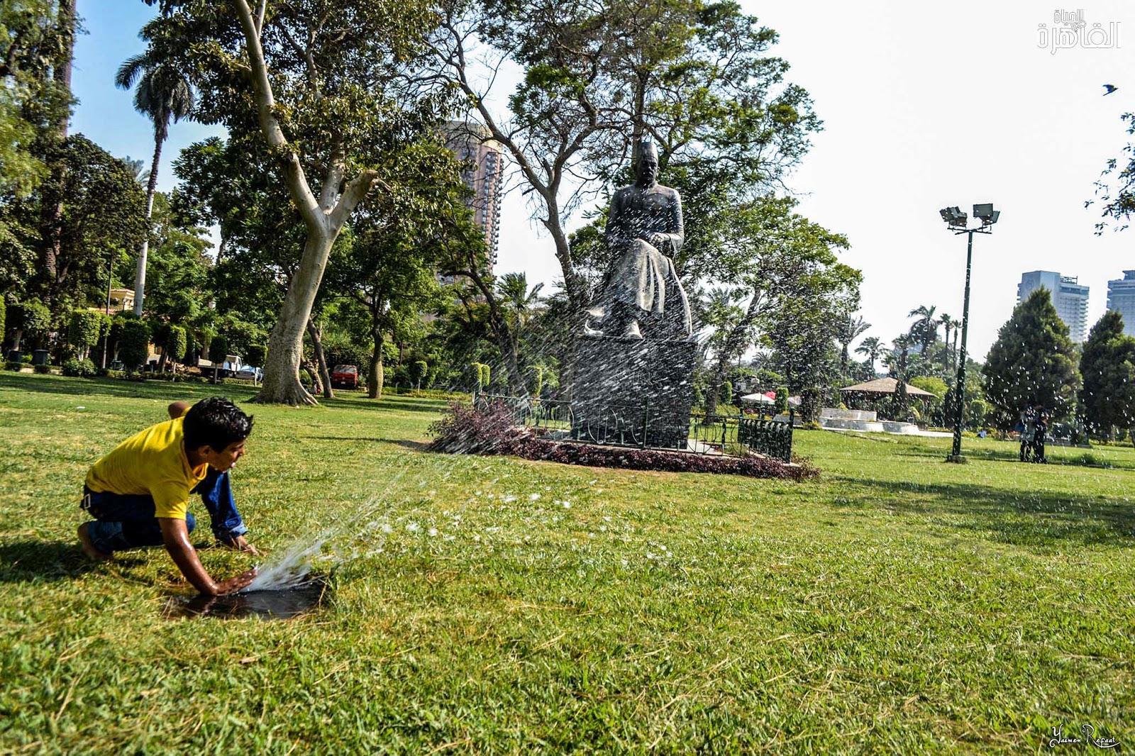 مع شدة حرارة يونية، وجد طفل متعته في اللهو بالمياة أمام تمثال حافظ إبراهيم - حديقة الحرية والصداقة - الحياة في القاهرة