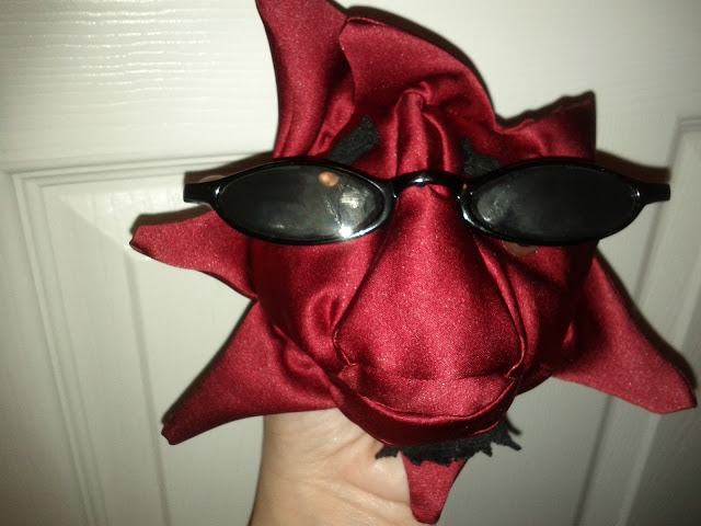 The red satin star is now complete.  He has rays protruding out from him, a large nose and lips, a black goatee and eyebrows and black sunglasses.  This is Big Daddy.