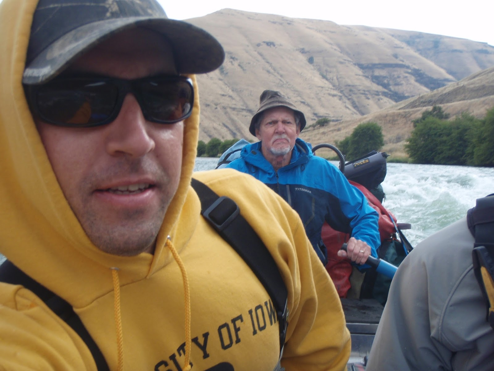 Picture of Dave and Doug Stewart in a drift boat on the Deschutes River with the semi-arid canyon in the background.