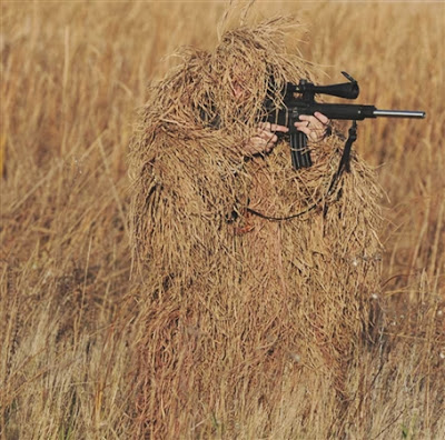 Man in ghillie suit hidden in weeds