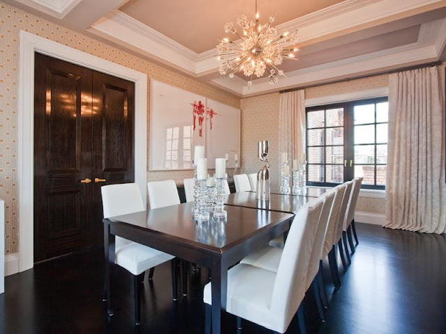 Dining room in an apartment with coffered ceiling, dark wood floors, sputnik starburst chandelier, contemporary print wallpaper, black encasement windows with floor length curtains, dark wood double doors, and a piece of modern art