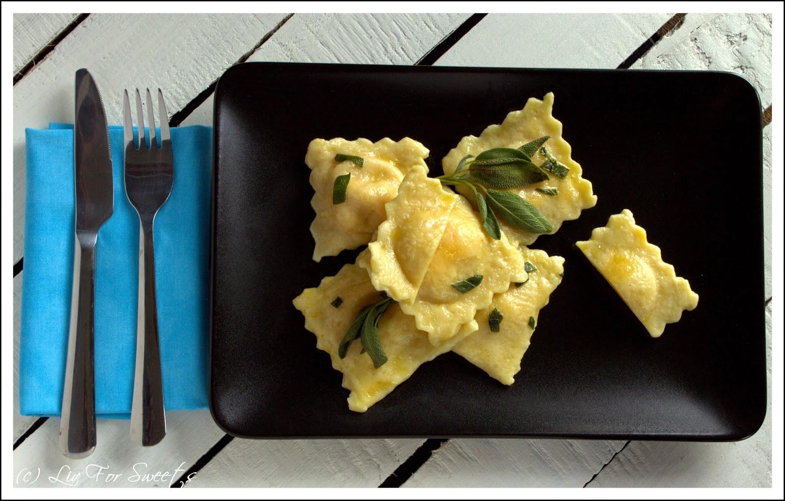 Kuerbis-Ricotta-Ravioli mit Salbei-Butter-Sauce auf schwarzem Teller, Besteck auf türkiser Serviette, Rezept, Thermomix, TM31