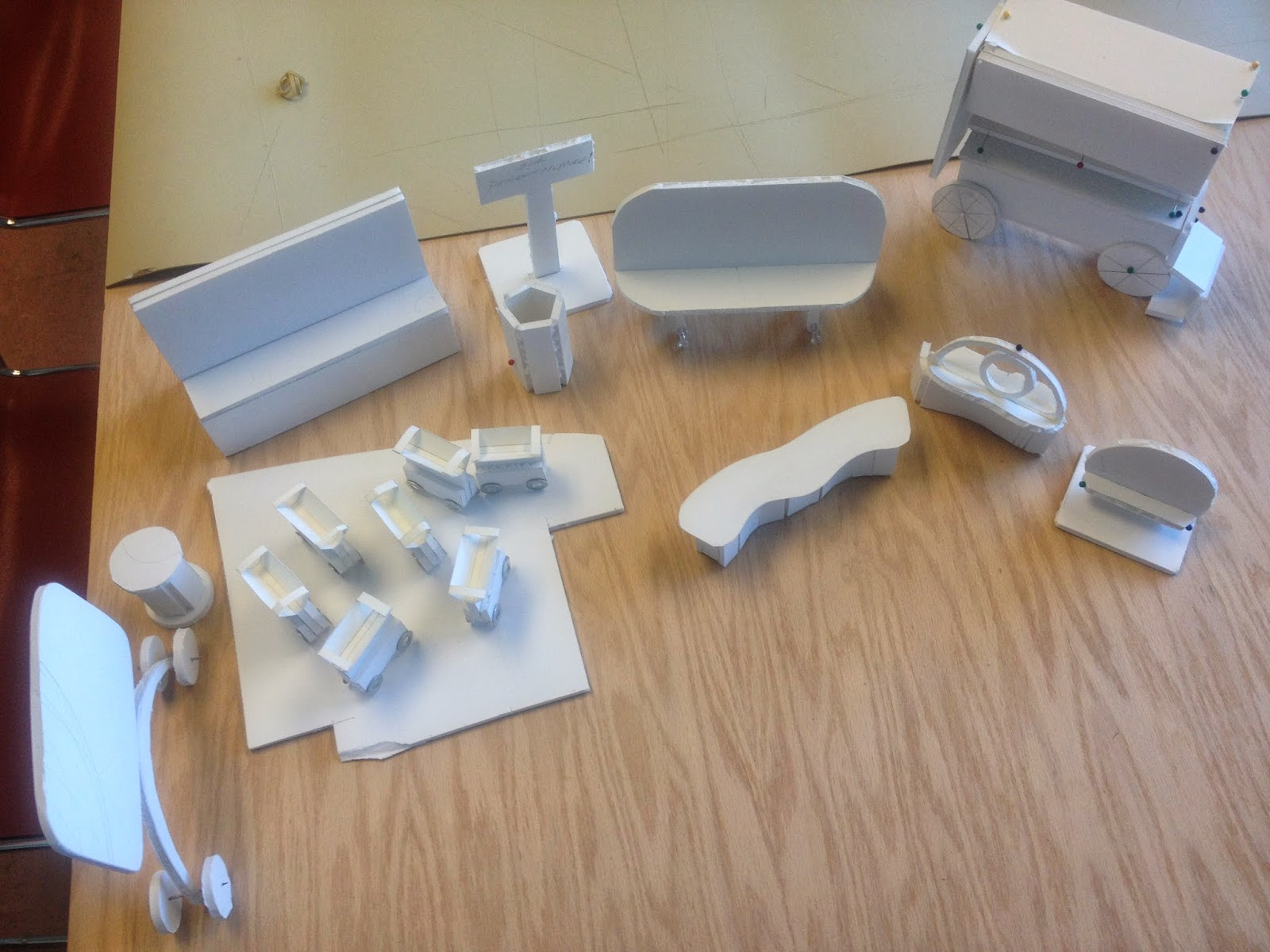 A top view image of white foam core model mockups grouped together on a wooden table.