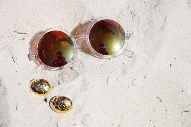 ASOS round mirrored sunglasses and clip-on earrings on sand.