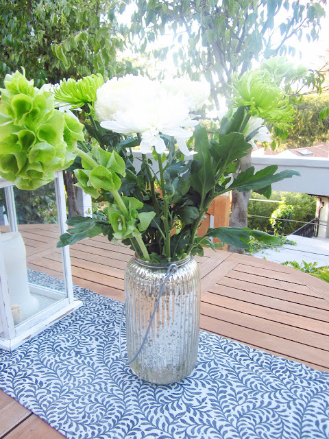 China Mums in white and some other green florals on dining table in a mercury glass hurricane lamp
