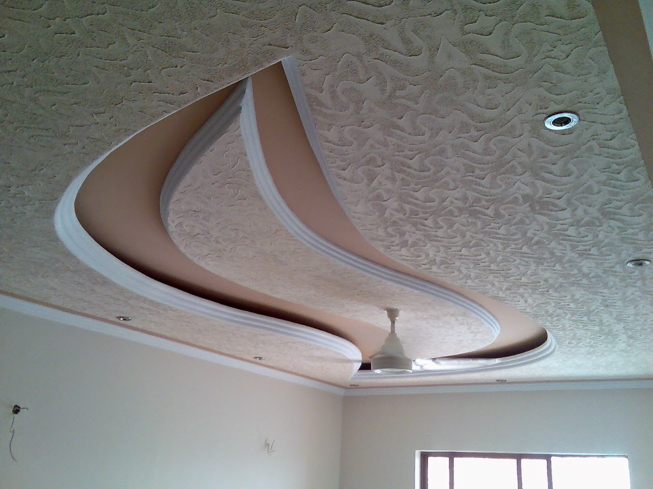 Simple bedroom ceiling designs made of gypsum with crystal chandelier - Curvy False Ceiling Designs Made Of Gypsum Board With Ceiling Fan