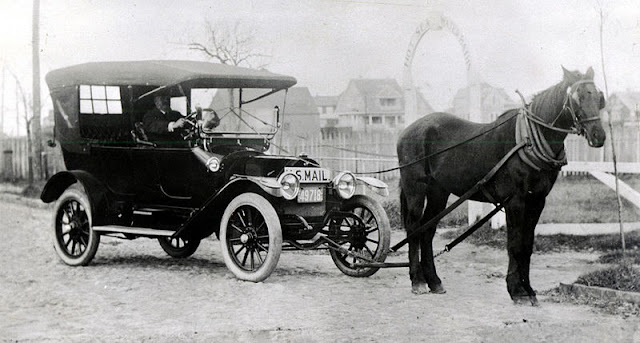 "Clinton Folger's ""Horsemobile"" delivering mail, on South Beach Street, at Hayden's Bath House entrance. For nearly twenty years, from 1900 to 1918, Nantucket was the only place in the nation that successfully fought encroachment of the automobile within its limits. Opposing politicians on the mainland and large property owners, mostly non-residents, Nantucketers kept the island free of the ""gasoline buggy"" until the final vote of the town on May 15, 1918. By the narrow margin of forty the automobile was allowed entry. Clinton Folger was the mail carrier for Nantucket. Because cars were forbidden by the town, he towed his car to the state highway for driving to Siasconset. Source: Nantucket Historical Association"