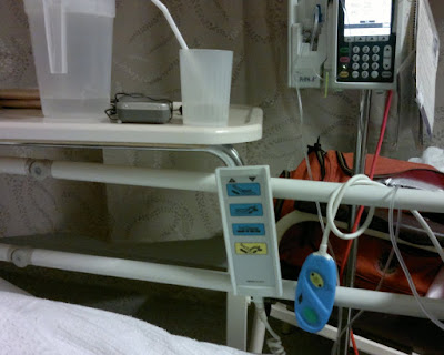 The view from my hospital bed clockwise from top left: overway table upon which is a water jug, transistor radio and glass of water with straw; infusion pump; over the sides of the bed hang the tubing for the drip, the nurse call bell and the bed controller.