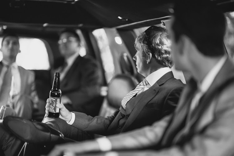 groom drinking a beer on the way to the wedding in the limousine