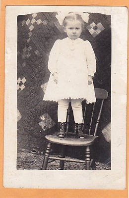 Little girl on chair in front of 9-patch quilt backdrop