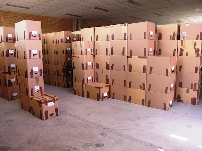 Rows of stacked and labelled cardboard cartons in a warehouse.