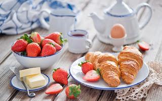 Desayuno con cuernitos croisant, fresas y matequilla con leche.