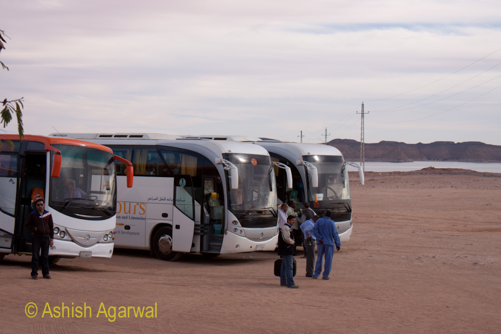 Tourists outside the buses parked with the water of Lake Nasser near the Abu Simbel temple