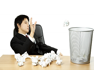 A bored man at work throws papers in a dustbin