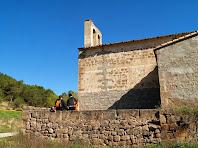 Al migdia, l'església de Merola, té un petit tancat de pedra amb un pedrís per seure-hi