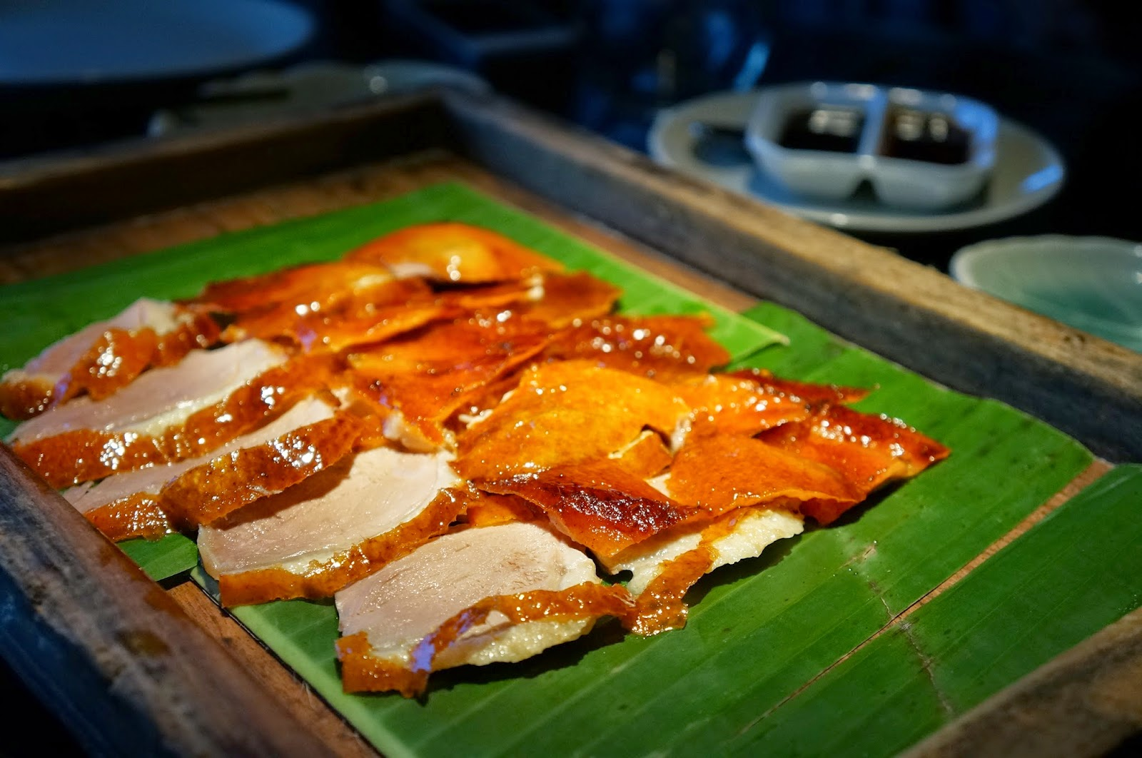 chef skilfully carved the thin crispy skin from the whole roasted duck at the table with just a modest layer of duck fat attached to the skin to give it aqua shard subdued lighting