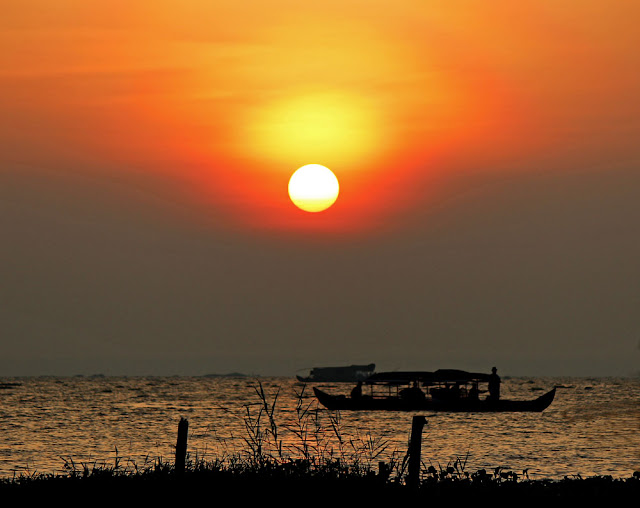 sun setting on Lake Vembanad in Kerala, India