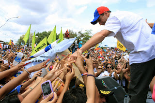 Presidential hopeful Henrique Capriles reaches out to supporters at a rally