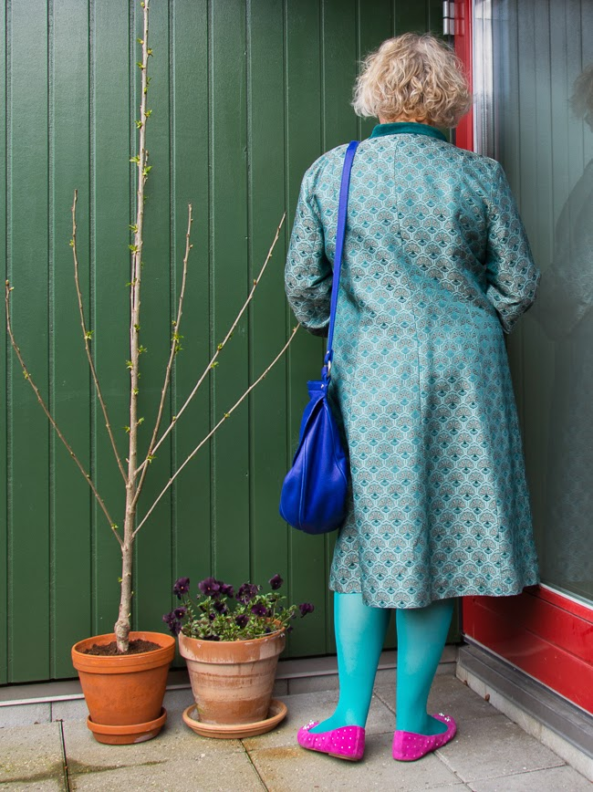 Backside of Kaffesoester in teal brocade coat on the way to bloggers market