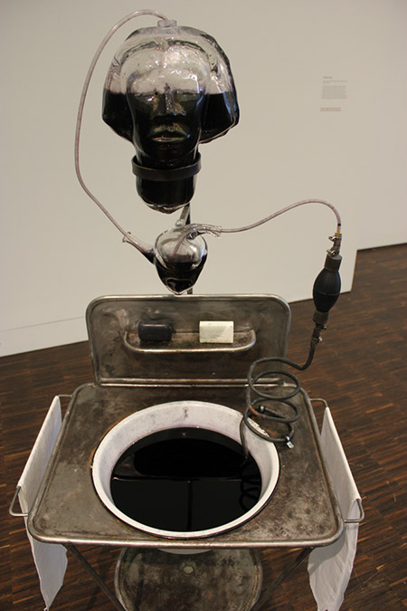 "Photograph by Robin Peters of a Sink filled with a black liquid.  Above the sink, suspended by metal ""still-like"" tubing is a glass heart and above that a glass head half filled with black liquid.  A bar of white soap and black soap on the old styled sink."