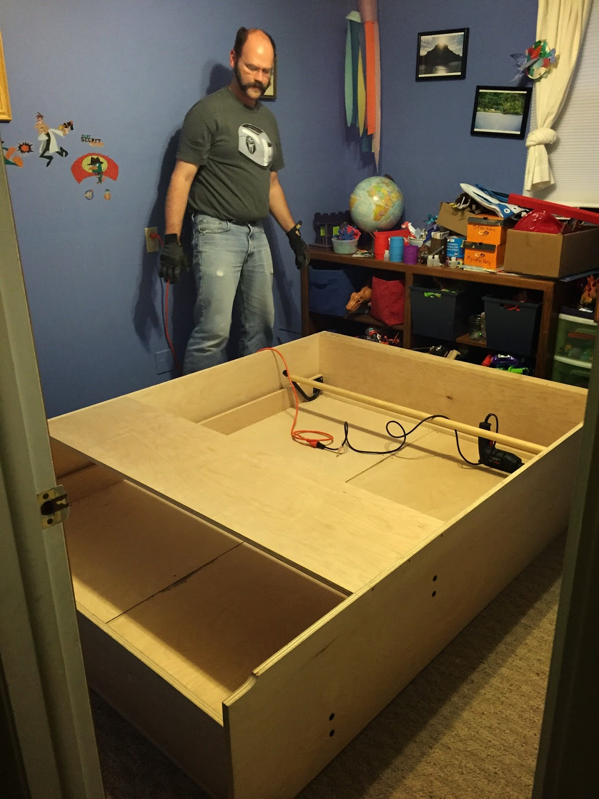 Chris standing next to the Murphy bed and frame while assembling it in the playroom guest room.