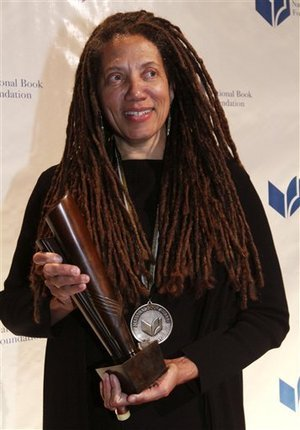 Black woman with long dreads stands smiling, holding Nation Book Award statuette and wearing NBA medal