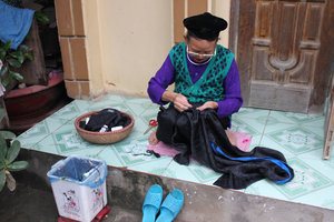 A Tày ethnic woman is sewing dress