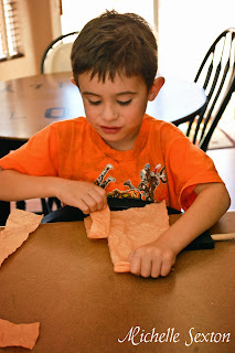 preschooler tearing tissue paper