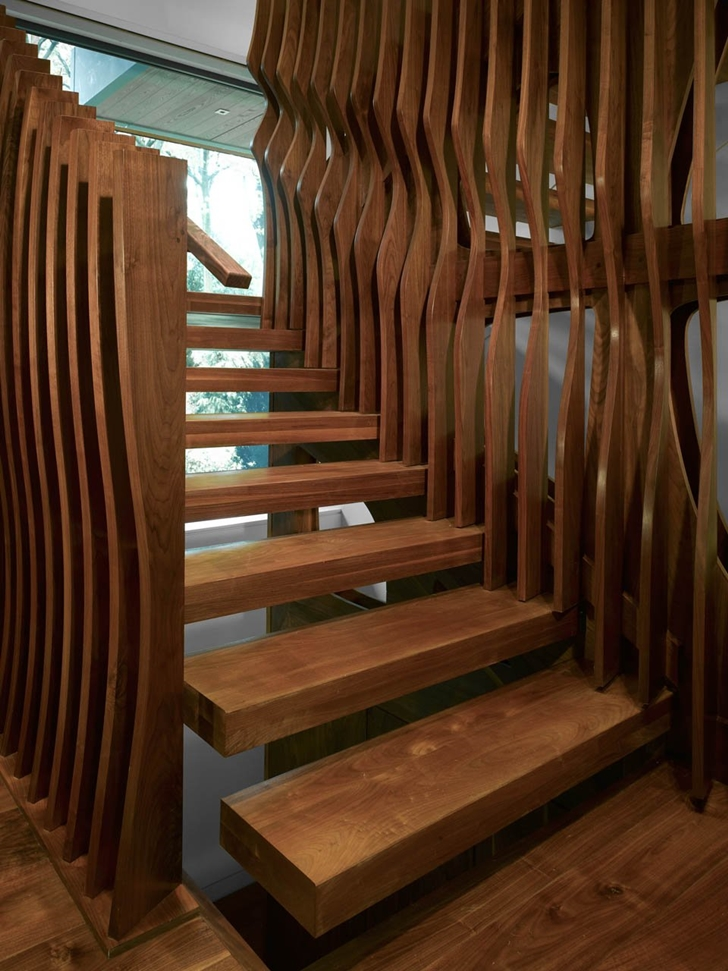 Wooden stairs in Modern mansion by Belzberg Architects Group