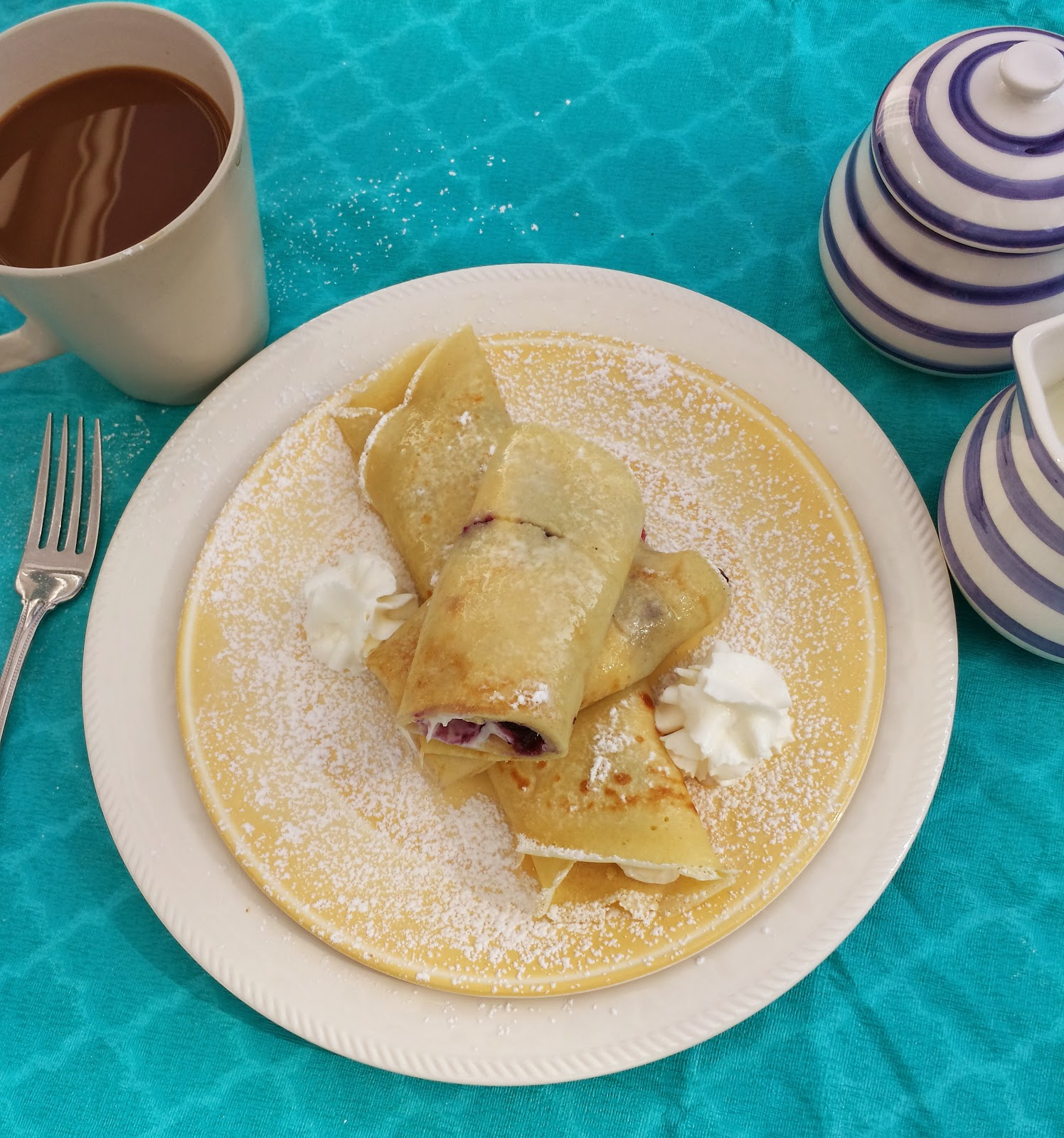 blueberry cream filled crepes with a cup of coffee