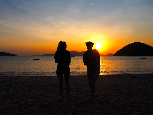 Silhouettes of two girls on the beach, against the sunset over the ocean on Repulse Bay Beach, Hong Kong