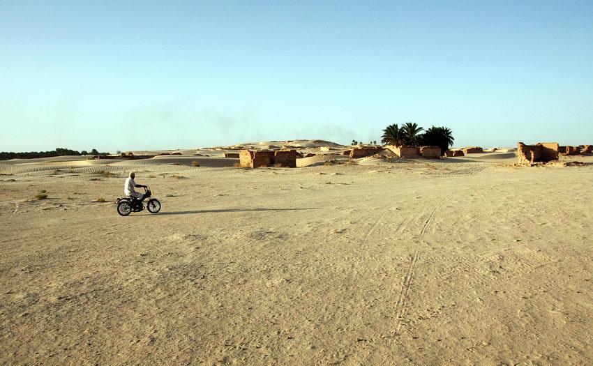 Paisagem desértica com um homem numa motorizada em circulação