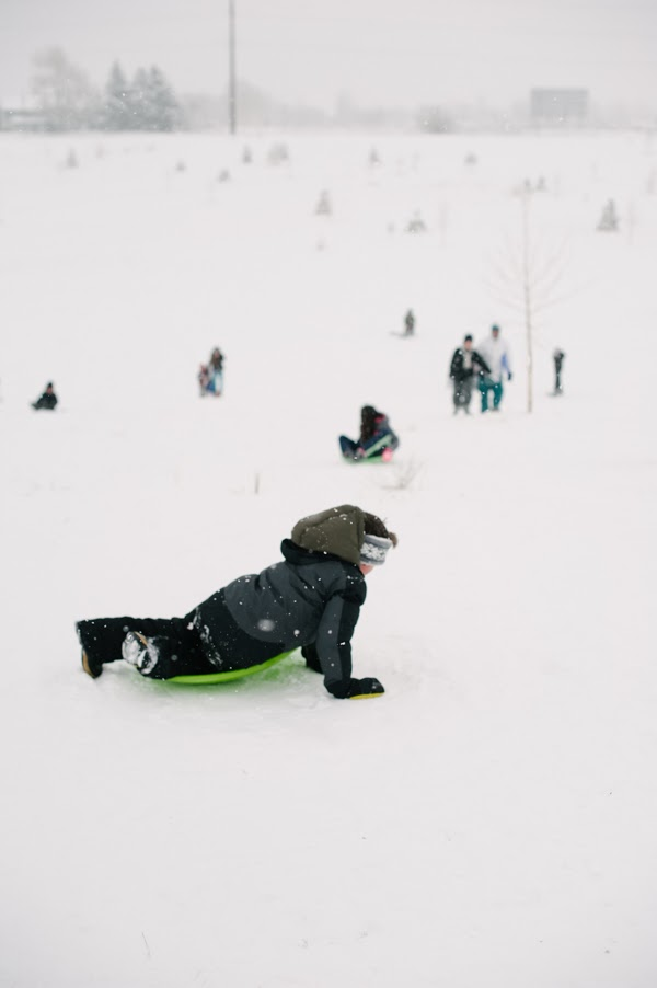 boy sledding down hill in green disc