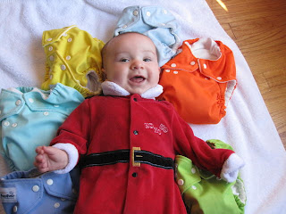 Baby in Santa Suit posed with cloth diapers