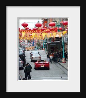 A red hot Ferrari tours through Chinatown in San Francisco.